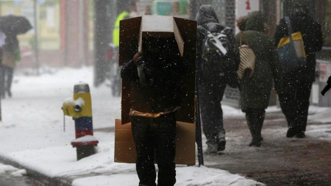A man stands with a box over his head as it snows in the Queens borough of New York