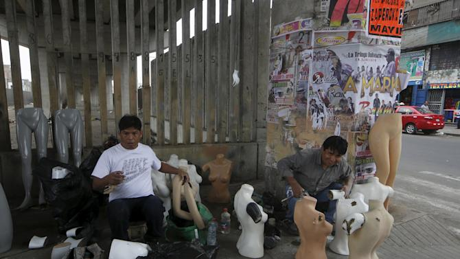 Men sell mannequins under the railway track of the Metro train in downtown Lima