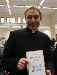 "Pope Benedict XVI's personal secretary Georg Ganswein poses with a copy of the Pope's book ""The Childhood of Jesus"" during a presentation in Vatican November 20, 2012. REUTERS/Alessandro Bianchi"