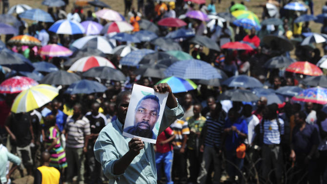 """FILE- In this Saturday, Oct. 6, 2012, file photo, striking mineworkers take part in a demonstration in Rustenburg, South Africa. The National Union of Mineworkers is accusing Anglo American Platinum of displaying """"racism"""" as the impasse between striking miners and the world's top platinum producer escalates. (AP Photo)"""