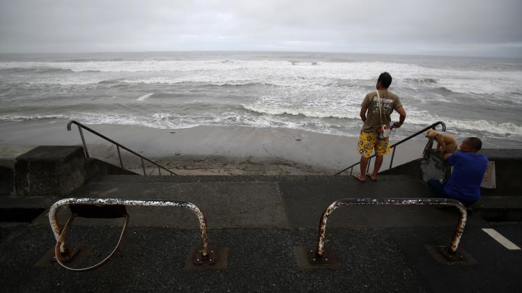 People look at the sea as tropical storm Neoguri approaches in Kamakura