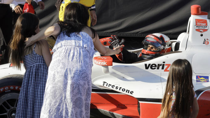 Juan Pablo Montoya, of Colombia, celebrates with his family after winning the IndyCar Firestone Grand Prix of St. Petersburg auto race Sunday, March 29, 2015, in St. Petersburg, Fla.  (AP Photo/Chris O'Meara)