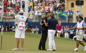 Stenson of Sweden shakes hands with playing partner Dubuisson of France after winning the DP World Tour Championship in Dubai