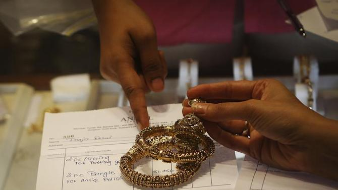 An employee explains the bill to a customer as gold bangles are placed on top of it inside a jewellery showroom in Mumbai