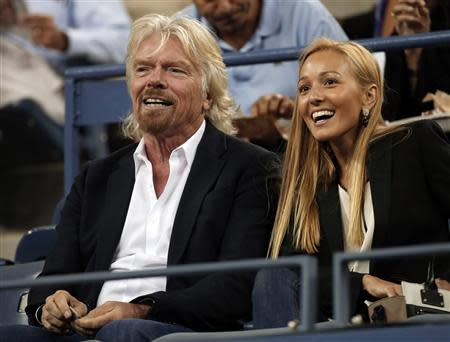 Virgin Group founder Branson of Britain sits with Ristic, girlfriend of Serbian tennis player Djokovic, at the U.S. Open tennis championships in New York
