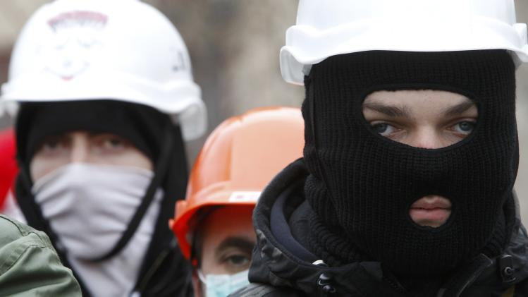 People wear helmets and masks as they attend a rally organized by supporters of EU integration at Maidan Nezalezhnosti or Independence Square in central Kiev