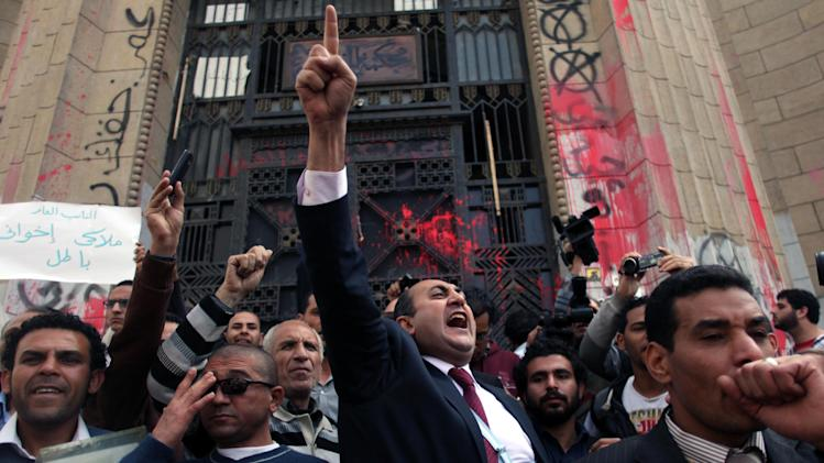 """FILE - In this Tuesday, March 26, 2013 file photo, Former presidential candidate Khaled Ali, center, chants slogans during a protest in front of the general prosecutor's office in Cairo, Egypt. Ali says he will not take part in upcoming presidential elections, calling them a """"farce."""" (AP Photo/Khalil Hamra, File)"""