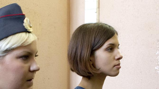 Nadezhda Tolokonnikova, right, a member of feminist punk group Pussy Riot is escorted to a court room in Moscow, Russia, Friday, Aug. 17, 2012. Security is tight around the Moscow courthouse where three members of the feminist punk band Pussy Riot are to hear the verdict Friday in a trial that could send them to prison for seven years. (AP Photo/Misha Japaridze)