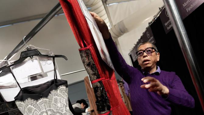 Designer Tadashi Shoji hangs one of the dresses backstage before his Fall 2013 collection was modeled during Fashion Week in New York,  Thursday, Feb. 7, 2013. (AP Photo/Richard Drew)