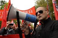 Russian opposition leader Sergei Udaltsov uses a loudspeaker to addresse the anti-Putin protest in Moscow. Tens of thousands of Russian opposition supporters have thronged the streets of Moscow to keep up the momentum of their challenge to Vladimir Putin&#39;s rule four months into his new mandate