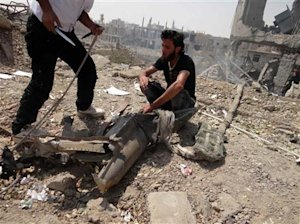 Free Syrian Army fighters inspect the remains of a jet fighter in Deir al- Zor