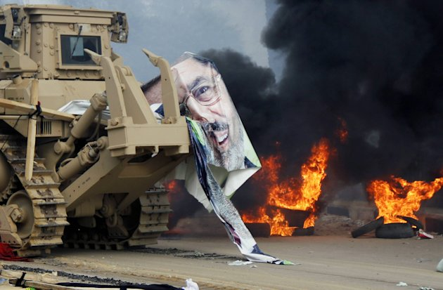 A torn poster of deposed Egyptian President Mursi is pictured as riot police clear the area of his supporters at Rabaa Adawiya square, where the protesters had been camping, in Cairo