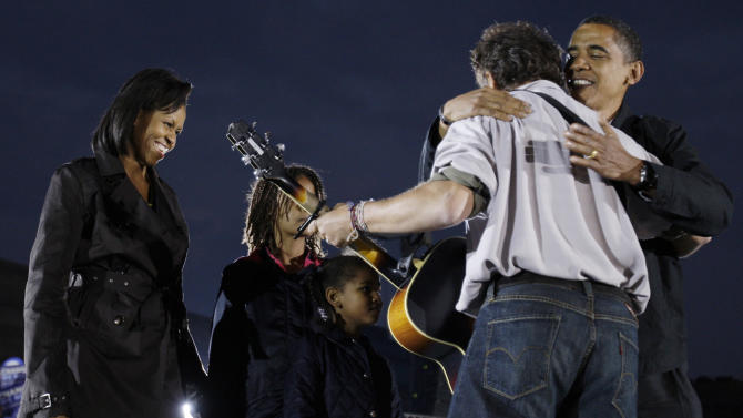 FILE - In this Nov. 2, 2008, file photo Democratic presidential candidate Sen. Barack Obama, D-Ill., on stage with his wife Michelle Obama and daughters Malia and Sasha, hugs Bruce Springsteen at a rally at the Cleveland Mall, in Cleveland, Ohio. Springsteen is hitting the campaign trail again on President Barack Obama's behalf, and he'll be joined this time by former President Bill Clinton at a rally in Parma, Ohio, on Thursday, Oct. 18, 2012. (AP Photo/Alex Brandon, File)