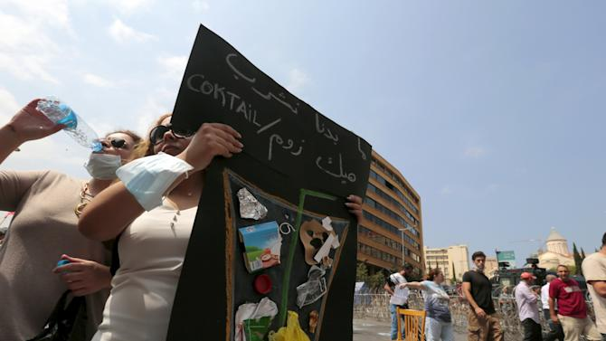 A woman carries a banner in protest against a rubbish collection problem near the government palace in Beirut