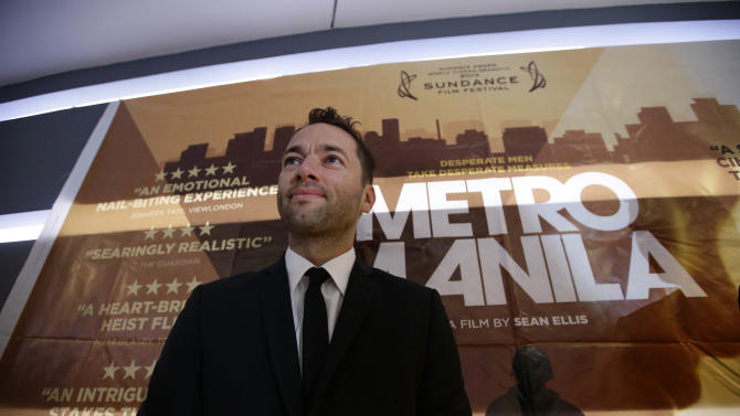 """In this Thursday Oct.3, 2013 photo, Briton Sean Ellis, writer-director of """"Metro Manila"""" - Britain's nominee to the Oscar Awards' best foreign language film, poses by his film's poster prior to its premier screening at a cinema in Taguig city, east of Manila, Philippines. (AP Photo/Bullit Marquez)"""