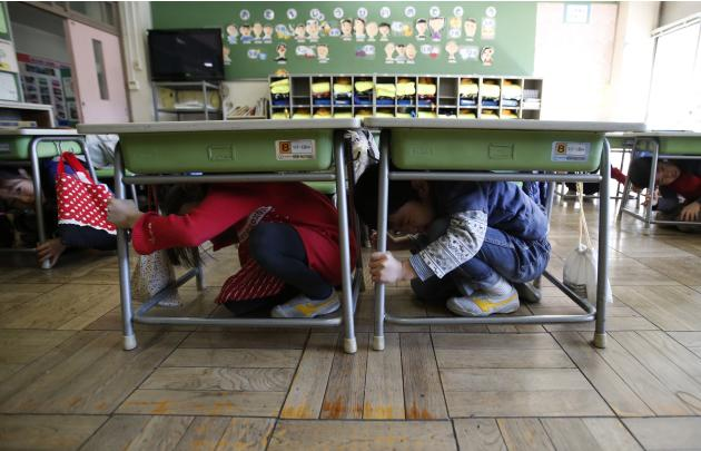 Students take shelter under desks during an earthquake simulation exercise at an elementary school in Tokyo