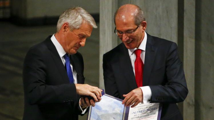 Nobel Peace Prize committee head Jagland hands over to Uzumcu, director general of the OPCW, the medal and the diploma during the Nobel Peace Prize awards ceremony at the City Hall in Oslo