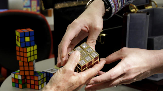 Erno Rubik, left, the inventor of the Rubik's Cube, reaches out to receive a gold and gemstone version of his cube from jeweler Fred Cuellar at Liberty Science Center, Wednesday, April 25, 2012, in Jersey City, N.J. The center will have an exhibit on the toys and will include the diamond version, which is worth 2.5 million dollars. (AP Photo/Julio Cortez)