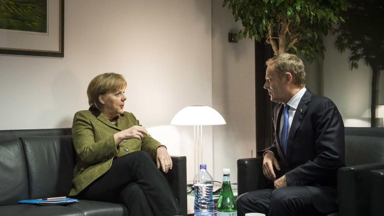 Poland's PM Tusk speaks with German Chancellor Merkel during their bilateral talks in Brussels