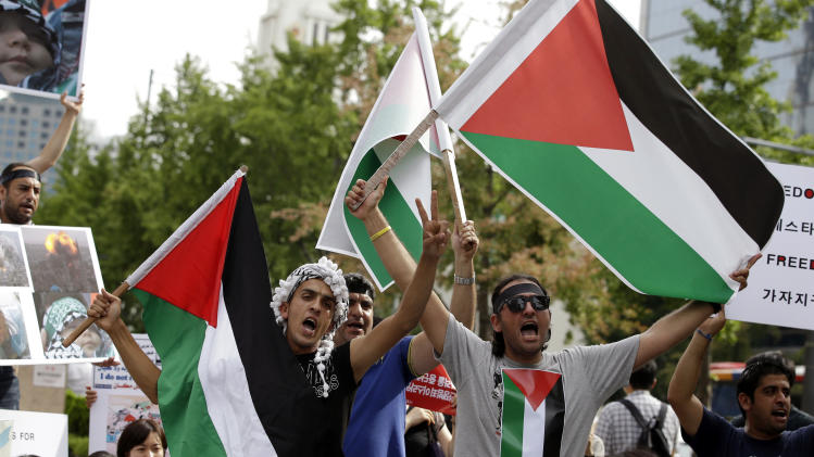 People from the Middle East countries and now living in South Korea, and South Korean activists shout slogans during a rally against the Israeli military operations in Gaza and wish for peace, in Seoul, South Korea, Saturday, Aug. 2, 2014. (AP Photo/Lee Jin-man)