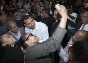 New York Yankees baseball player Alex Rodriguez poses for a photo with a supporter after leaving Major League Baseball's headquarters in New York