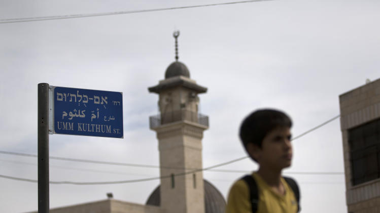 In this Oct. 24, 2012, a Palestinian child walks past the newly-named Umm Kulthum street in east Jerusalem. In stark contrast to the orderly western half of the city, the often rundown, predominantly Arab neighborhoods of east Jerusalem have for decades existed without street signs or house numbers _ a phenomenon that has caused confusion for many. That confusion may be eased with a new push to have all the winding streets and alleys of east Jerusalem named. The municipality has named 145 since last year, with the rest expected to be identified by 2013. (AP Photo/Bernat Armangue)