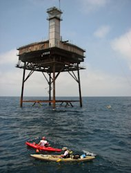This undated photo provided by the General Services Administration shows kayakers near the Diamond Shoals Light Tower, located 13 miles off Cape Hatteras, N.C. David Schneider of Richfield, Minn., bought the light tower from the federal government for $20,000. He plans to visit for the first time in November, and hopes to use the tower's 5,000-square-feet of space for various research projects. (AP Photo/General Services Administration)