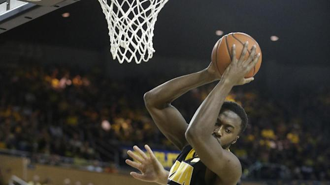 Iowa center Gabriel Olaseni (0) pulls down a rebound during the first half of an NCAA college basketball game against Michigan at Crisler Arena in Ann Arbor, Mich., Sunday, Jan. 6, 2013. (AP Photo/Carlos Osorio)