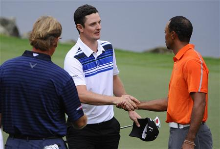 Ernie Els of South Africa, Justin Rose of England, and Tiger Woods of the U.S. finish up on the 18th hole during the second round play in the Arnold Palmer Invitational PGA golf tournament in Orlando