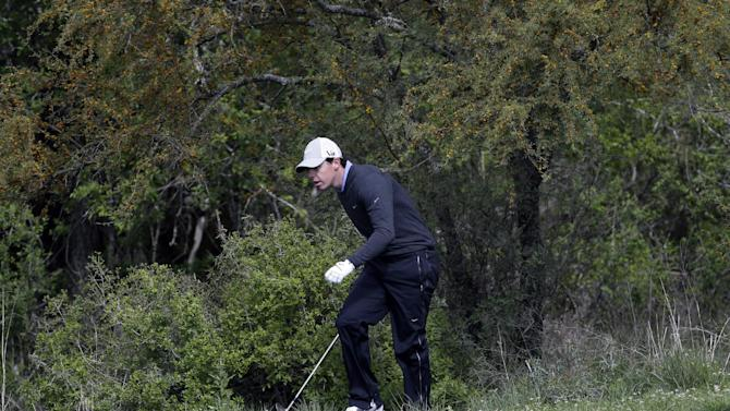 Rory McIlroy, of Northern Ireland, looks for his ball in the woods on the second hole during the first round of the Texas Open golf tournament, Thursday, April 4, 2013, in San Antonio.  (AP Photo/Eric Gay)