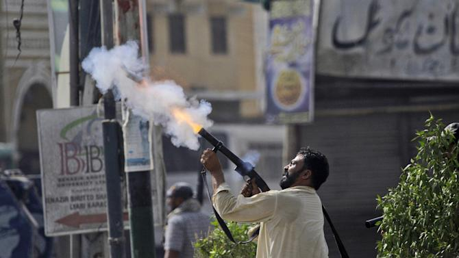 """In this Wednesday, May 2, 2012, photo, a plainclothes Pakistani police officer fires a tear gas canister at a hideout of criminals, during a crackdown operation against criminals in Karachi, Pakistan. For months, the Supreme Court's Chief Justice Iftikhar Chaudhry has been leading special hearings on Karachi's crime, berating the city's top police officers for failing to act. The past week, he demanded they move in to clean up so-called """"no-go"""" areas _ entire neighborhoods where police fear to tread _ according to local press reports. (AP Photo/Shakil Adil)"""
