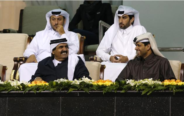 Former Emir of Qatar Sheikh Hamad speaks with PSG Chairman Al-Khelaifi as they watch the Qatar Open tennis match between Rafael Nadal and Peter Gojowczyk in Doha