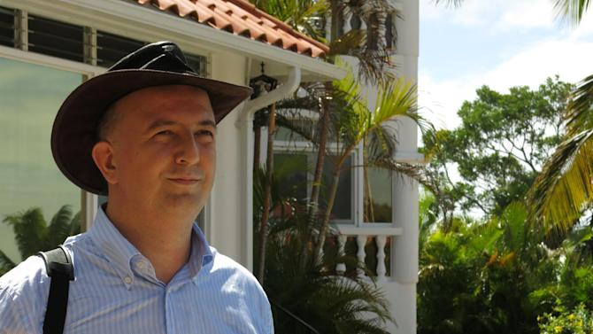 In this Aug 26, 2013 photo, Ulrich Mühl, spokesman of the German spiritualist group Academy for Future Health poses for a photo outside Peter Brunck's home, the leader of the organization, in Sosua, Dominican Republic. Muhl dismissed allegations anything sinister was going on at the home. Brunck faces charges for the creation of a supposed armed group and was temporally detained during a heavily armed October raid at the residential compound. (AP Photo/Ezequiel Abiu Lopez)