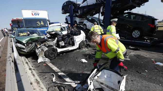 A rescue worker works amongst the wreckage of some of the 100 vehicles involved in multiple collisions, which took place in dense fog during the morning rush hour, on the Sheppey Bridge in Kent, east of London