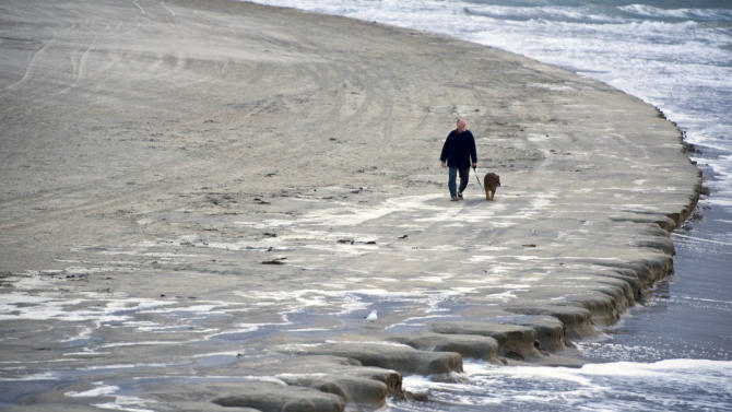 A man walks his dog along the beach early Thursday morning, Jan. 10, 2013 just south of the Newport Beach pier, as a king tide erodes the beach and strong winds and cold temperatures move into Orange County, Calif. King tide is a popular term used to refer to an especially high tide. (AP Photo/Orange County Register, Mark Rightmire) /// ADDITIONAL INFORMATION: 01/08/13 - Mark Rightmire, The Orange County Register