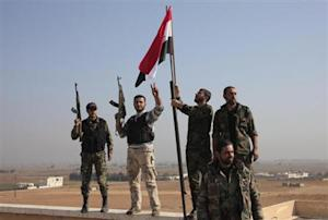 Forces loyal to Syria's President Assad erect a national flag at al-Azizieh village after capturing it from rebels