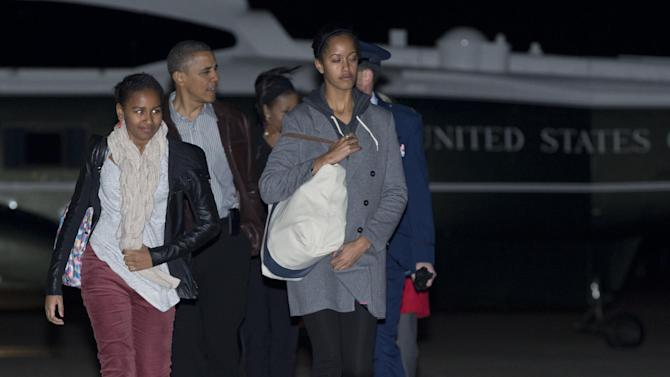 President Barack Obama, First Lady Michelle Obama and their daughters Malia and Sasha walk from Marine One to board Air Force One, Friday, Dec. 21, 2012, in Andrews Air Force Base, Md., en route to a holiday vacation in Honolulu. (AP Photo/Carolyn Kaster)