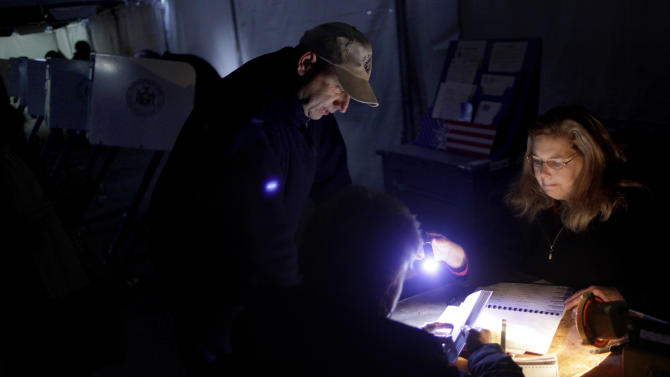 Poll worker Lisa Amico, right, helps voters by flashlight in a dark and unheated tent serving as a polling site in the Midland Beach section of Staten Island, New York, Tuesday, Nov. 6, 2012. The original polling site, a school, was damaged by Superstorm Sandy. (AP Photo/Seth Wenig)