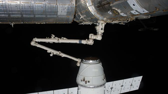 In this image provided by NASA the SpaceX Dragon commercial cargo craft is grappled by the Canadarm2 robotic arm at the International Space Station May 25, 2012. Expedition 31 Flight Engineers Don Pettit and Andre Kuipers grappled Dragon at 9:56 a.m. (EDT) and used the robotic arm to berth Dragon to the Earth-facing side of the station's Harmony node at 12:02 p.m. Friday May 25, 2012. Dragon became the first commercially developed space vehicle to be launched to the station. Dragon is scheduled to spend about a week docked with the station before returning to Earth on May 31 for retrieval.  (AP Photo/NASA)