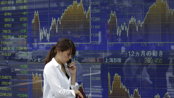 A woman speaks on a mobile phone in front of a securities firm's electronic stock board in Tokyo Monday, June 25, 2012. Asian stocks mostly drifted lower Monday as investors grew cautious ahead of a critical European Union summit later this week where Greek leaders will attempt to renegotiate some terms of the country's international bailout. Japan's Nikkei 225 index was 0.4 percent lower at 8,765.54. (AP Photo/Shizuo Kambayashi)