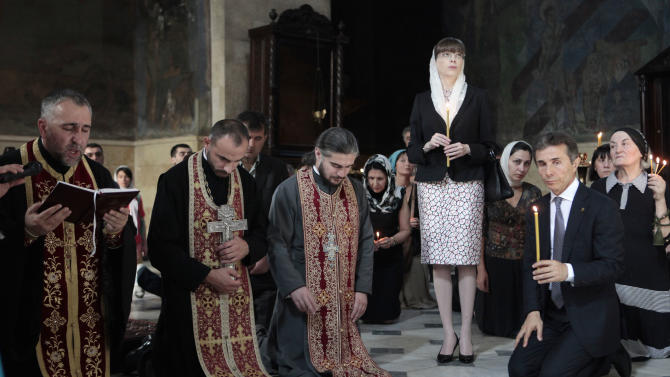 Georgia's billionaire and opposition leader Bidzina Ivanishvili, right,  and his wife Ekaterine Khvedelidze prays  in a church  in Tbilisi, Georgia, Monday, Oct. 1, 2012. Voters in Georgia are choosing a new parliament in a heated election Monday that will decide the future of Saakashvili's government. (AP Photo/Georgy Abdaladze)