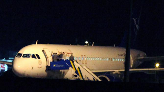 People gather atop the aircraft steps at a Syrian passenger plane that was forced by Turkish jets to land at Esenboga airport in Ankara, Turkey, Wednesday, Oct. 10, 2012. Turkish jets on Wednesday forced a Syrian Air Airbus A320 passenger plane to land at Ankara airport on suspicion that it may be carrying weapons, Turkey's Foreign Minister Ahmet Davutoglu said, amid heightened tensions between Turkey and Syria that have sparked fears of a wider regional conflict.(AP Photo/Burhan Ozbilici)
