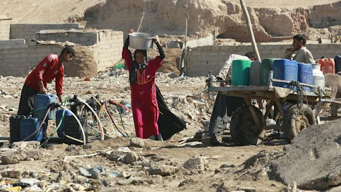 Iraqis fill drinking and cooking water containers from a public water hose on open ground in Baghdad's eastern suburb of Fadaliayah, Iraq, Tuesday, Oct. 30, 2012. The neighborhood has no municipal water supply. The US allocated billions of dollars to rebuild Iraq's water infrastructure shattered by war, sanctions and neglect,  but security issues, corruption and inefficiency have left millions of Iraqis still without basic sanitation or piped water. (AP Photo/Hadi Mizban)