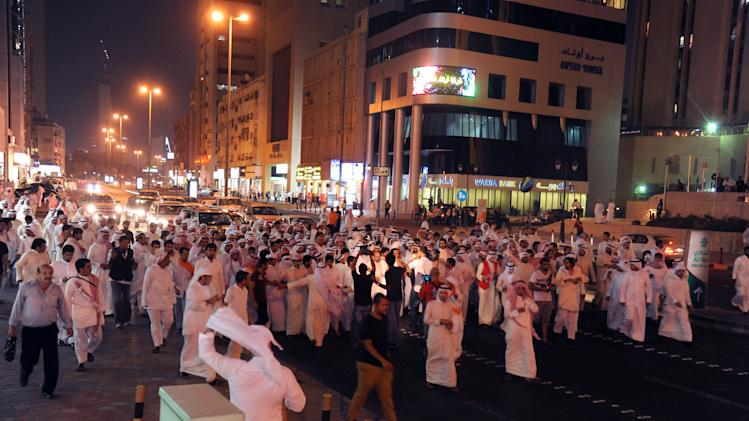 Kuwaiti men walk down Fahed Al Salem Street during a demonstration in Kuwait City on Sunday, October 21, 2012. Several thousand protestors from opposition groups, Bedouin tribes and former MPs gathered in different points of Kuwait City to demonstrate against the Government's amendment of the country's electoral law.(AP Photo/Gustavo Ferrari)