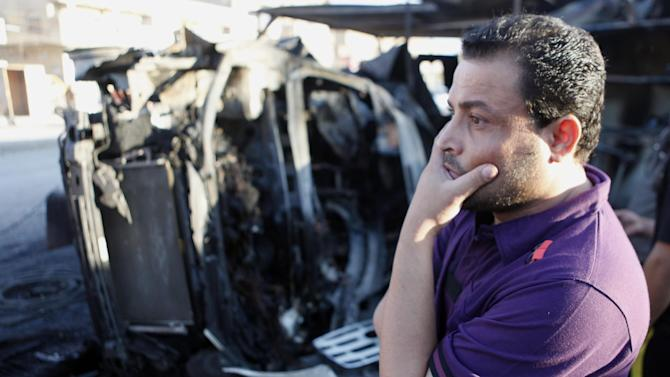 A man inspects the aftermath of Saturday's car bomb explosion, in the Shiite enclave of Sadr City, in Baghdad, Iraq, Sunday, Oct. 28, 2012. Iraqi insurgents unleashed a string of bombings and other attacks primarily targeting the country's Shiite community on Saturday, Oct. 27, 2012, in a challenge to government efforts to promote a sense of stability by preventing attacks during a major Muslim holiday, killed and wounded scores of people. (AP Photo/Karim Kadim)