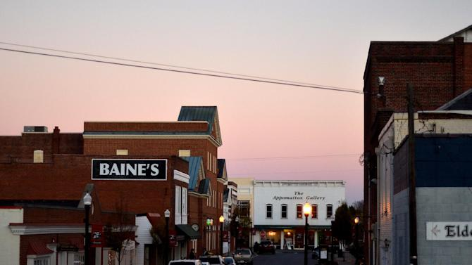"""This Thursday, Nov. 8, 2012 photo shows the sun setting over Main Street in Appomattox, Va. Signs around town call it the place """"where our nation reunited"""" as the Civil War came to an end. But listen to people here and all over the country, or look at exit polls from the election, and you confront deep division, polarization. Red or blue. Left or right. Big government or small. Tea party or Occupy. Ninety-nine percent or one. Employed or out-of-work. Citizen or non-citizen. Black or white or brown. (AP Photo/Pat Jarrett)"""