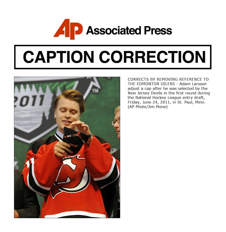 CORRECTS BY REMOVING REFERENCE TO THE EDMONTON OILERS - Adam Larsson adjust a cap after he was selected by the New Jersey Devils in the first round during the National Hockey League entry draft, Friday, June 24, 2011, in St. Paul, Minn. (AP Photo/Jim Mone)