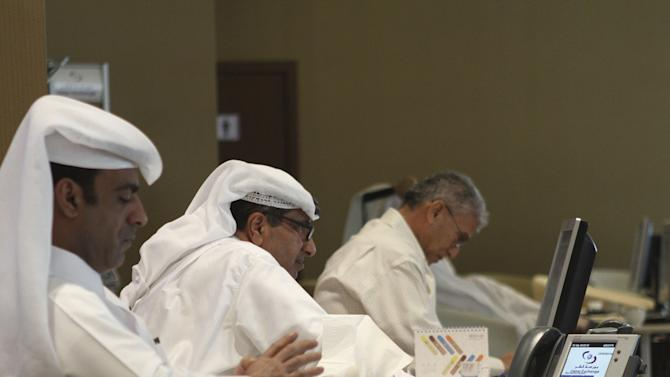 Traders look at share prices on their monitors at the Doha Stock Exchange