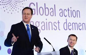 Britain's Prime Minister David Cameron watched by Health Secretary Jeremy Hunt, speaks at the G8 Dementia Summit, at Lancaster House in central London