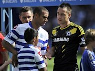 Queens Park Rangers' Anton Ferdinand (L) avoids shaking hands with John Terry ahead of their English Premier League match on September 15. Terry was cleared of criminal charges relating to the incident by a court in July